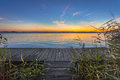 Blue And Orange Sunset Over Boardwalk On The Shore Of A Lake Stock Photo - 51000930