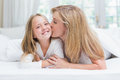 Mother Kissing Her Daughter On The Cheek In The Bed Stock Photography - 51085432