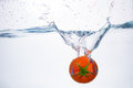 Red Tomato Dropped Into Blue Water On White Stock Photos - 51171903