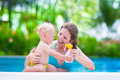 Mother Applying Sun Screen On Baby In Swimming Pool Stock Photos - 51250613