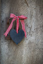 Black Heart With A Red White Checked Ribbon Hanging On An Old Do Royalty Free Stock Images - 51378679
