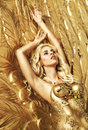 Blond Sensual Lady Lying On The Gold Wings Royalty Free Stock Images - 51409379
