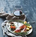 Wine Appetizer Set. Glass Of Red Wine, Vintage Dinnerware, Brushetta With Cherry, Dried Tomatoes, Arugula, Parmesan, Smoked Meat O Stock Photo - 51476760