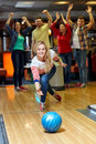 Happy Young Woman Throwing Ball In Bowling Club Stock Photography - 51495002