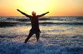 Jumping For Joy In The Sunset On The Ocean Stock Photography - 51498552