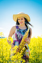 Woman With Saxophone In Rapeseed Field Royalty Free Stock Image - 51519526