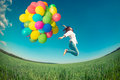 Woman Jumping With Toy Balloons In Spring Field Stock Photo - 51679910