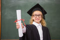 Pupil With Graduation Robe And Holding Her Diploma Royalty Free Stock Photography - 51707477