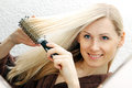 Young Smiling Woman Brushing Her Long Blond Hair Stock Image - 51781081