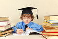 Little Boy In Academic Hat Writing Pen In Notebook Among The Old Books Stock Photos - 51963363