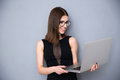 Smiling Woman Standing With Laptop Over Gray Background Stock Photography - 51964042