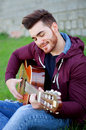 Cool Handsome Guy Playing Guitar At Outside Stock Images - 52090384