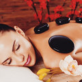 Adult Woman Relaxing In Spa Salon With Hot Stones On Back Royalty Free Stock Images - 52188889