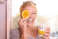 Laughing Woman Holding An Orange To Her Eye Royalty Free Stock Photo - 52220515