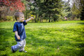 Happy Young Boy Walking In A Park Holding Out A Dandelion Flower Royalty Free Stock Photos - 52234628
