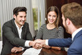 Smiling Young Couple Shaking Hands With An Insurance Agent Royalty Free Stock Photo - 52422965