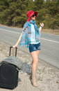 Young Woman With A Suitcase Is Hitchhiking On  The Road Pointing Stock Photos - 52434283