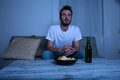 Young Man Watching TV At Nighttime With Chips And Beer Stock Photos - 52435713