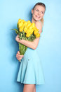 Happy Girl With Yellow Tulips. Blue Background Royalty Free Stock Photos - 52493818