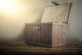 Old Wooden Chest With Open Lit On Wooden Tabletop Against Grunge Stock Images - 52501564
