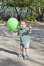 Happy Little Cute Boy Holds Green Balloon And Smiles Stock Photo - 52634590