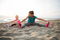 Healthy Mother And Baby Girl Stretching On Beach Royalty Free Stock Images - 52675149