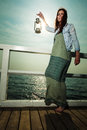 Young Woman On Pier With Oil Kerosene Lamp. Stock Photography - 52811752