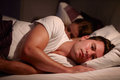 Man Lying Awake In Bed Suffering With Insomnia Stock Image - 52852761