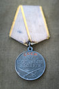Soviet Medal For Combat Service And Two Red Carnations. Royalty Free Stock Photography - 52992587