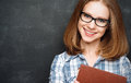 Happy Girl Student With Glasses And Book From Blackboard Stock Photos - 53128533