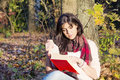 Portrait Of A Beautiful Woman Leaning On A Tree With Book In The Autumn Park Stock Photos - 53169403