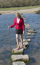 Stepping Stones Woman Walking Across River Royalty Free Stock Photo - 53173365