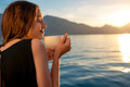 Young Woman Drinking Coffee On The Pier At Sunrise Stock Photography - 53303382