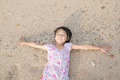 Asian Smiling Cute Little Girl Lying On The Beach Sand. Thai Chi Royalty Free Stock Photo - 53431515