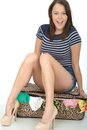 Attractive Happy Young Woman Sitting On A Packed Overflowing Suitcase Stock Images - 53534854