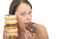 Attractive Natural Happy Young Woman Eating A Pile Of Iced Donuts Stock Photo - 53538610
