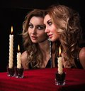 Beautiful Young Woman Looking In The Mirror Near Three Candles Stock Image - 53577941