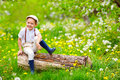 Cute Happy Kid Sitting On Wooden Stump In Spring Garden Royalty Free Stock Photos - 53614558