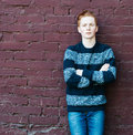 Young Redhead Man In A Sweater And Jeans Standing Next To A Brick Wall With Folded Arms Royalty Free Stock Image - 53745486