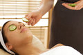 Young Woman Lying On Massage Table With Cucumber Slice Being Placed Over Eye Royalty Free Stock Photos - 53755328