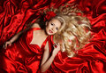 Hair Model, Fashion Woman Blonde Lying On Red Silk Cloth Stock Photography - 53955522
