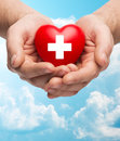 Male Hands Holding Red Heart With White Cross Royalty Free Stock Photography - 54035417