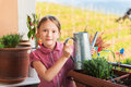 Adorable Little Girl Watering Plants On The Balcony Stock Image - 54145261
