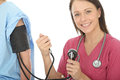 Happy Young Professional Female Doctor Taking The Blood Pressure Of A Patient Stock Photo - 54155790