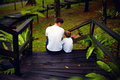 Father And Son Sitting On Wooden Stairs In Rain Forest Royalty Free Stock Photography - 54230717