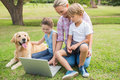 Happy Family With Their Dog Using Laptop Stock Photo - 54257400