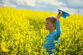 Young Boy With Paper Plane Against Blue Sky And Yellow Field Flo Stock Photo - 54265860