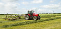 A Farm Tractor Raking Hay Silage In Field Stock Images - 54364074