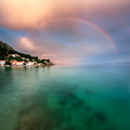 Rainbow Over Rocky Beach And Small Village After The Rain Stock Photo - 54404620
