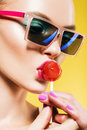 Woman Eating Big Red Lollipop In Blue Sunglasses Royalty Free Stock Photos - 54427418